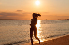 Σκιαγραφία μιας νέας γυναίκας που τρέχει στην παραλία στο ηλιοβασίλεμα στοκ εικόνα με δικαίωμα ελεύθερης χρήσης