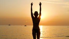 Σκιαγραφία μιας νέας γυναίκας σε ένα καπέλο στην παραλία κατά τη διάρκεια του ηλιοβασιλέματος, το οποίο στέκεται σε ένα μαγιό και απόθεμα βίντεο