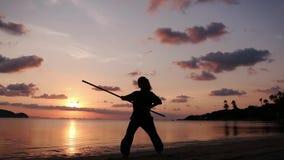 Σκιαγραφία μιας νέας ισχυρής γυναίκας που στέκεται στην παραλία με ένα ραβδί kung-fu