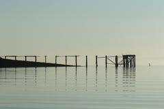 Σκιαγραφία μιας στάσης επάνω στον οικότροφο κουπιών δίπλα σε ένα μακροχρόνιο ξύλινο pi Στοκ φωτογραφία με δικαίωμα ελεύθερης χρήσης