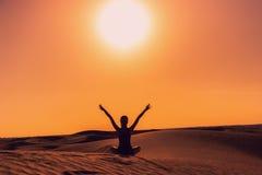 Σκιαγραφία μιας συνεδρίασης κοριτσιών στην άμμο που αυξάνει τα όπλα της επάνω κατά τη διάρκεια του ηλιοβασιλέματος στοκ φωτογραφία με δικαίωμα ελεύθερης χρήσης