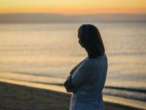 Σκιαγραφία μιας όμορφης γυναίκας στο υπόβαθρο του ήλιου ρύθμισης βραδιού Στοκ Φωτογραφία