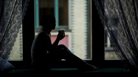 Σκιαγραφία νέου Brunette που εγκαθιστά στο Windowsill Η στοχαστική γυναίκα εξετάζει το παράθυρο κρατώντας ένα φλυτζάνι με απόθεμα βίντεο