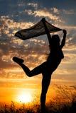 Σκιαγραφία νέων κοριτσιών με το σάλι που χορεύει στο υπόβαθρο του όμορφου νεφελώδους ουρανού με το πορτοκαλί ηλιοβασίλεμα στοκ εικόνες