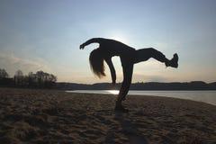 Σκιαγραφία νέων κοριτσιών στα μαύρα ενδύματα που χορεύουν, στην όχθη ποταμού Στοκ φωτογραφία με δικαίωμα ελεύθερης χρήσης
