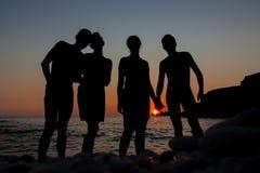 Σκιαγραφία ομάδας των νέων στο υπόβαθρο της παραλίας και της θάλασσας ηλιοβασιλέματος Στοκ Φωτογραφία