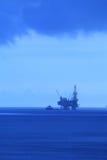 Σκιαγραφία ο παράκτιος Jack επάνω στην εγκατάσταση γεώτρησης διατρήσεων και τη βάρκα (BlueTone) Στοκ Εικόνες