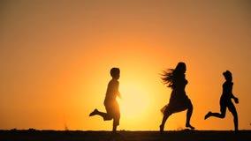 Σκιαγραφία πέντε παιδιών που τρέχουν στο λόφο με το ηλιοβασίλεμα απόθεμα βίντεο