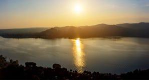 Σκιαγραφία πανοράματος των βουνών και η πόλη Arona στην Ιταλία στο ηλιοβασίλεμα και το νερό Στοκ Εικόνες