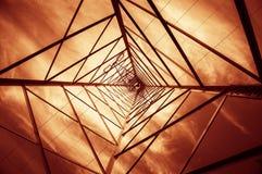 Σκιαγραφία που πυροβολείται των πυλώνων ηλεκτρικής ενέργειας με το νεφελώδη ουρανό Στοκ Φωτογραφίες