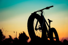 Σκιαγραφία ποδηλάτων βουνών στο όμορφο ηλιοβασίλεμα Στοκ Εικόνες