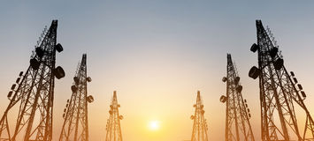 Σκιαγραφία, πύργοι τηλεπικοινωνιών με τις κεραίες TV και δορυφορικό πιάτο στο ηλιοβασίλεμα, σύνθεση πανοράματος Στοκ εικόνες με δικαίωμα ελεύθερης χρήσης
