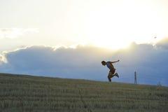 Σκιαγραφία σχεδιαγράμματος του νεαρού άνδρα που τρέχει στην επαρχία που ασκεί την τελική ορμή στο ηλιοβασίλεμα στοκ εικόνες με δικαίωμα ελεύθερης χρήσης
