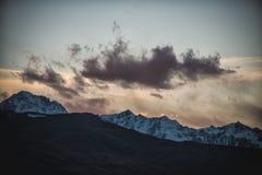 Σκιαγραφία σύννεφων ηλιοβασιλέματος βουνών χιονιού στοκ εικόνα