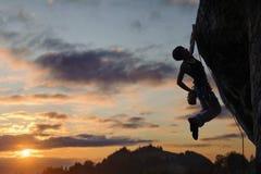 Σκιαγραφία της αθλητικής γυναίκας που αναρριχείται στον απότομο τοίχο βράχου στοκ φωτογραφίες
