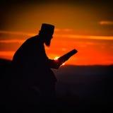 Σκιαγραφία της ανάγνωσης ιερέων στο φως ηλιοβασιλέματος Στοκ εικόνα με δικαίωμα ελεύθερης χρήσης