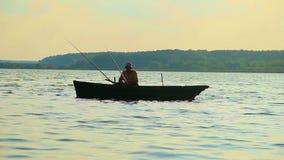 Σκιαγραφία της απομονωμένης συνεδρίασης ψαράδων στη βάρκα, εξοπλισμός αλιείας απόθεμα βίντεο