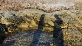 Σκιαγραφία της γυναίκας και του άνδρα στην ακτή πετρών απόθεμα βίντεο