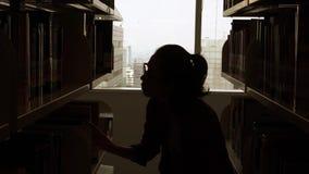 Σκιαγραφία της γυναίκας που επιδιώκει ένα βιβλίο στη βιβλιοθήκη φιλμ μικρού μήκους
