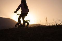 Σκιαγραφία της γυναίκας που οδηγά ένα ποδήλατο στοκ φωτογραφία