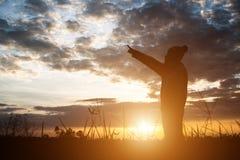 Σκιαγραφία της γυναίκας που στέκεται στον τομέα κατά τη διάρκεια του ηλιοβασιλέματος Στοκ εικόνες με δικαίωμα ελεύθερης χρήσης