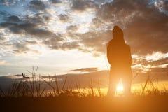 Σκιαγραφία της γυναίκας που στέκεται στον τομέα κατά τη διάρκεια του ηλιοβασιλέματος Στοκ φωτογραφία με δικαίωμα ελεύθερης χρήσης
