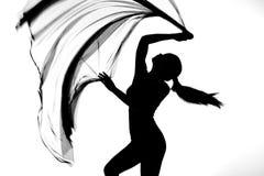 Σκιαγραφία της γυναίκας που χορεύει με το διαφανές ύφασμα στο Μαύρο και