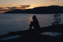 Σκιαγραφία της γυναίκας στην ακτή με τον ωκεανό και τα βουνά ενώ ήλιοι Στοκ Φωτογραφίες