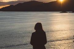 Σκιαγραφία της γυναίκας στην ακτή με τον ωκεανό και τα βουνά ενώ ήλιοι Στοκ φωτογραφίες με δικαίωμα ελεύθερης χρήσης