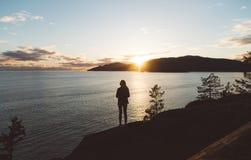 Σκιαγραφία της γυναίκας στην ακτή με τον ωκεανό και τα βουνά ενώ ήλιοι Στοκ Φωτογραφία