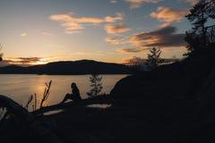 Σκιαγραφία της γυναίκας στην ακτή με τον ωκεανό και τα βουνά ενώ ήλιοι Στοκ φωτογραφία με δικαίωμα ελεύθερης χρήσης