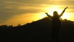 Σκιαγραφία της γυναίκας τουριστών οδοιπόρων με τα όπλα που αυξάνονται πάνω από το βουνό που εξετάζει την άποψη ηλιοβασιλέματος Κο απόθεμα βίντεο