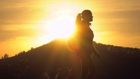 Σκιαγραφία της γυναίκας τουριστών οδοιπόρων με την οδοιπορία σακιδίων πλάτης στο βουνό στο ηλιοβασίλεμα Κορίτσι οδοιπόρων, θηλυκή απόθεμα βίντεο