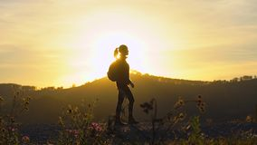 Σκιαγραφία της γυναίκας τουριστών οδοιπόρων με την οδοιπορία σακιδίων πλάτης στο βουνό στο ηλιοβασίλεμα Κορίτσι οδοιπόρων, θηλυκή φιλμ μικρού μήκους
