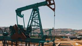 Σκιαγραφία της λειτουργώντας αντλίας πετρελαίου και ένα παλαιό σκουριασμένο βαρέλι σιδήρου πλησίον σε ένα υπόβαθρο του μπλε ουραν απόθεμα βίντεο