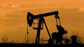 Σκιαγραφία της λειτουργώντας αντλίας πετρελαίου σε ένα υπόβαθρο των σύννεφων απόθεμα βίντεο
