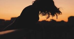 Σκιαγραφία της εκτίναξης γυναικών η τρίχα της στο ηλιοβασίλεμα σε μια πόλη απόθεμα βίντεο