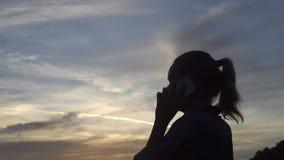 Σκιαγραφία της ευτυχούς γυναίκας που μιλά στο κινητό τηλέφωνο κατά τη διάρκεια της όμορφης ανατολής απόθεμα βίντεο