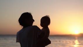 Σκιαγραφία της ευτυχούς οικογένειας - μητέρα και ήλιος στο ηλιοβασίλεμα φιλμ μικρού μήκους