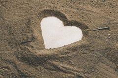 Σκιαγραφία της καρδιάς που σύρεται στον άργιλο άμμου στοκ εικόνα