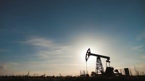 Σκιαγραφία της λειτουργώντας αντλίας πετρελαίου από την πετρελαιοφόρο περιοχή στο ηλιοβασίλεμα Ο βιομηχανικός εξοπλισμός φιλμ μικρού μήκους