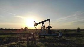 Σκιαγραφία της λειτουργώντας αντλίας πετρελαίου από την πετρελαιοφόρο περιοχή στο ηλιοβασίλεμα Ο βιομηχανικός εξοπλισμός απόθεμα βίντεο