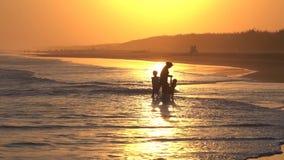 Σκιαγραφία της μητέρας και των παιδιών που παίζουν τα κύματα απόθεμα βίντεο