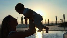 Σκιαγραφία της μητέρας με την λίγος γιος στα όπλα της στο ηλιοβασίλεμα Στοκ Εικόνες