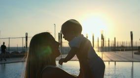 Σκιαγραφία της μητέρας με την λίγος γιος στα όπλα της στο ηλιοβασίλεμα Στοκ εικόνα με δικαίωμα ελεύθερης χρήσης