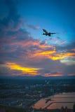 Σκιαγραφία της μύγας αεροπλάνων πέρα από τον ουρανό και την πόλη Στοκ εικόνες με δικαίωμα ελεύθερης χρήσης