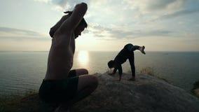 Σκιαγραφία της νέας γιόγκας άσκησης ζευγών στον απότομο βράχο στην ανατολή απόθεμα βίντεο