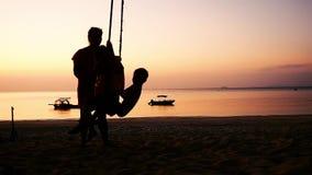 Σκιαγραφία της νέας μητέρας που ταλαντεύεται τα μικρά παιδιά στην ταλάντευση παραλιών στην παραλία ηλιοβασιλέματος κίνηση αργή 19 φιλμ μικρού μήκους