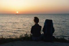 Σκιαγραφία της νέας συνεδρίασης γυναικών στην ακτή με ένα σακίδιο πλάτης στο υπόβαθρο ηλιοβασιλέματος Στοκ Εικόνες