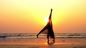 Σκιαγραφία της νέας gymnast γυναίκας που κάνει την ακροβατική τούμπα στην αμμώδη παραλία στο ηλιοβασίλεμα φιλμ μικρού μήκους